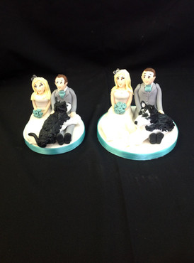 2 tier cake with the bride and groom on each and both of their dogs separately