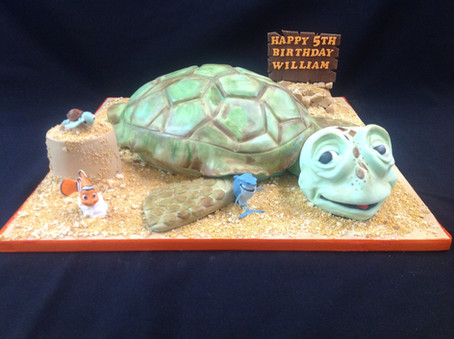 Finding Nemo themed birthday cake with a main focus on a turtle and the wording happy 5th birthday William