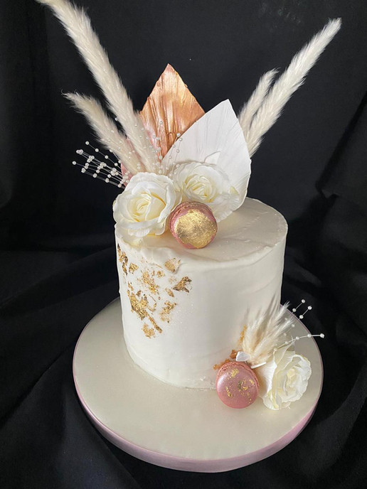white and gold cake decorated with flowers