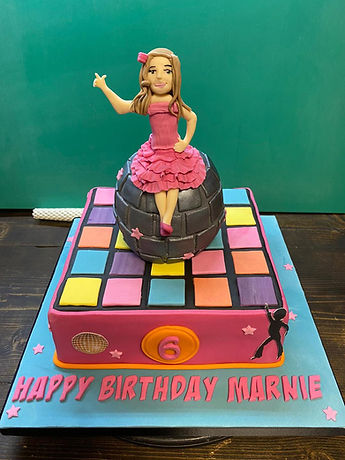 dance inspired cake with happy birthday marnie written on it and a dancer sat on top of a disco ball