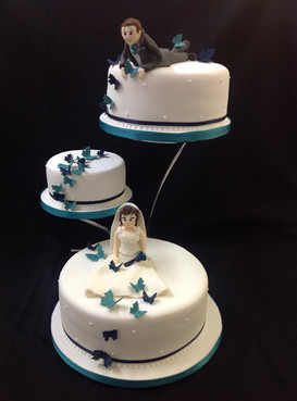 3 tier wedding cake with the groom on the top tier looking down at the bride on the bottom tier
