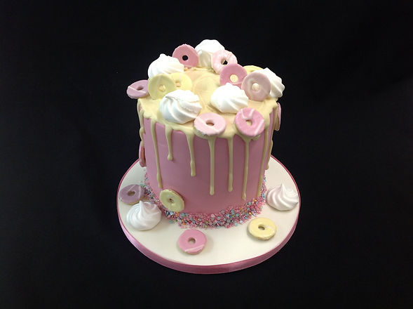 pink and yellow cake decorated with circular biscuits and mini meringues