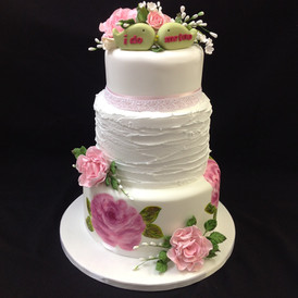 multi tier cake decorated with flowers and the wording I do and me too are on the top.