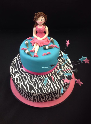 two tier black and white cake with pink and blue on the top tier and a lady sat on top