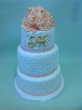a multi tier white cake with floral design and an s and h on the edge and pink flowers on top
