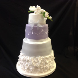 multi tier white and lilac cake with floral and pearl decoration