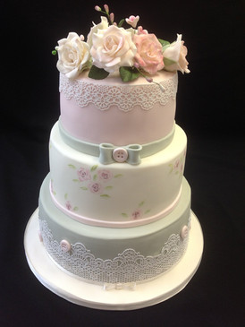 a multi-tier cake with silver ribbon around it and flowers on top