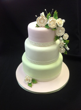 a multi tier cake with flowers decorating it