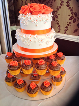 orange and white cake decorated with daisies and surrounded by cupcakes