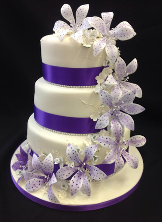 white and purple cake with multiple tiers decorated with flowers