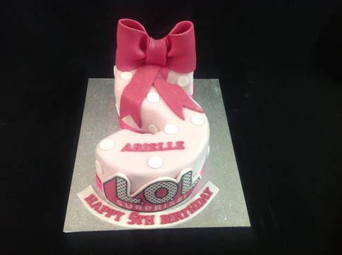 a pink and white LOL cake in the shape of the number 5 for a happy 5th birthday