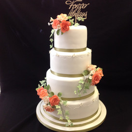 4 tier white and gold cake with floral decoration