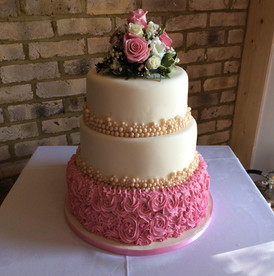 a multi-tier pink white and gold cake decorated with pearls and flowers