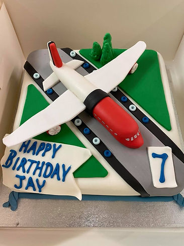 a 7th birthday cake with a passenger plane on a runway