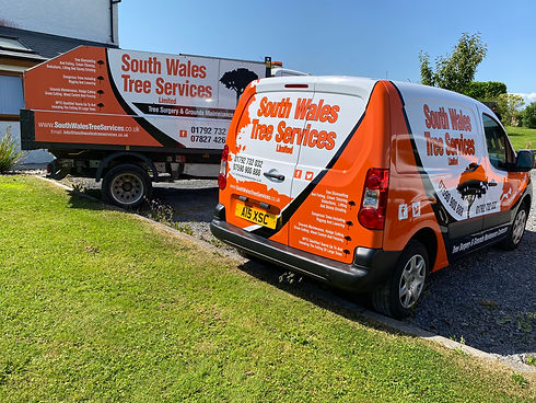 2 south wales tree services vehicles parked in front of a lawn