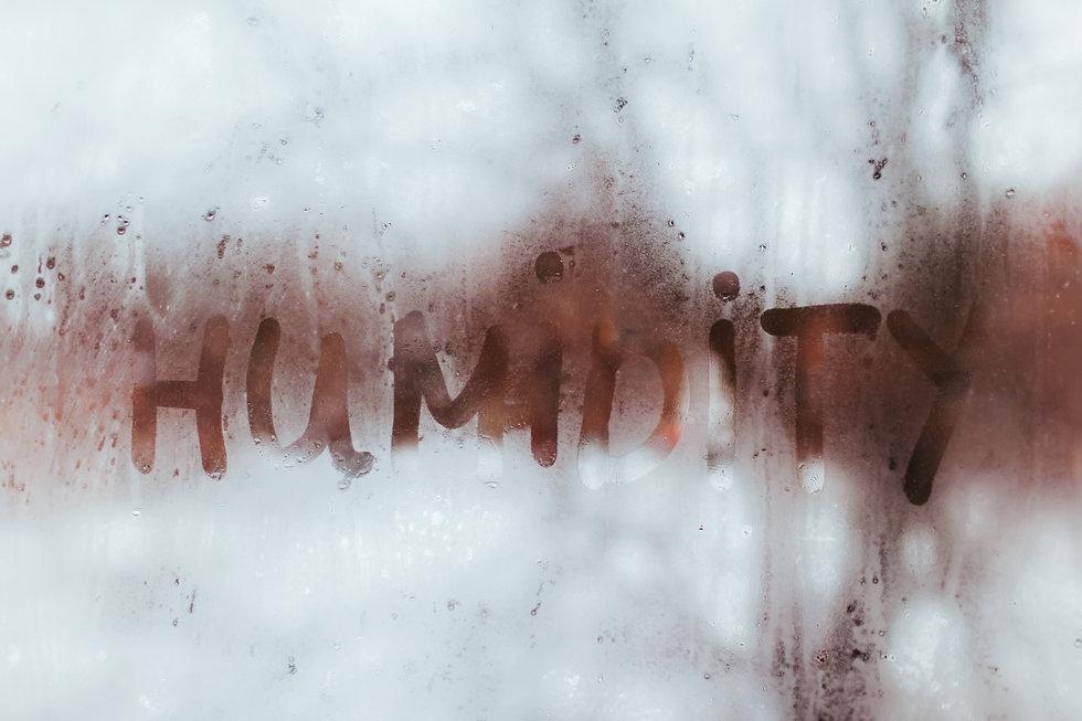 Humidity word written on wet window. Hig