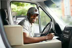 kxp driver smiling with kxp cap in truck