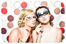 two-girls-in-a-photo-booth-with-masks.jp