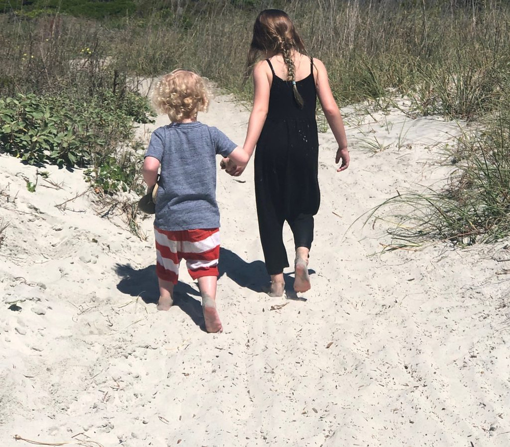 kids walking along the beach hand in hand