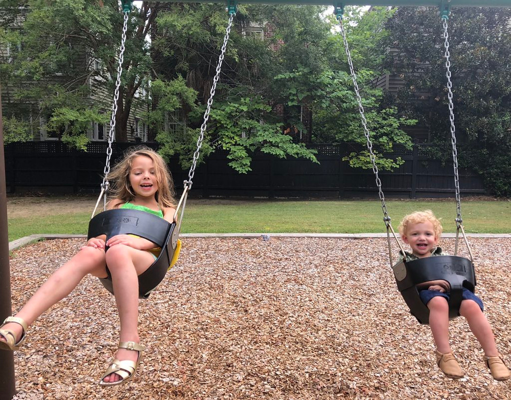 children swinging at Tiedemann Park in Charleston, South Carolina
