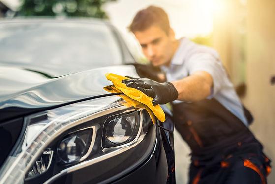 Mann reinigt sein Auto mit einem Mikrofasertuch