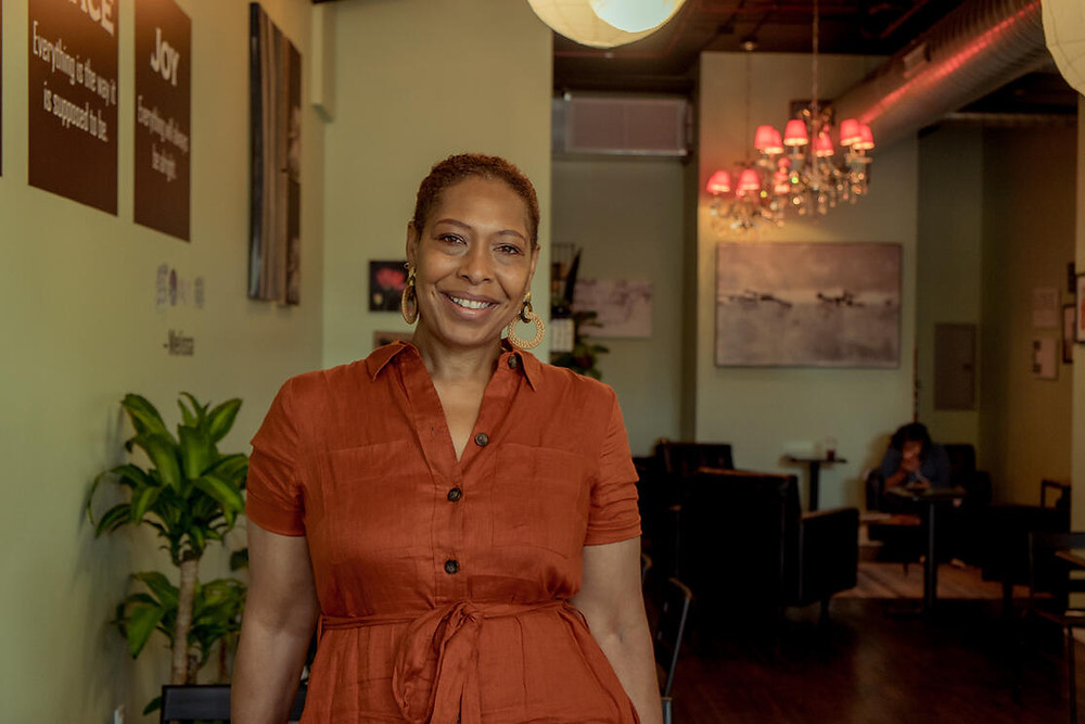 Owner Melissa of UnBAR Cafe stands in front of a seating area