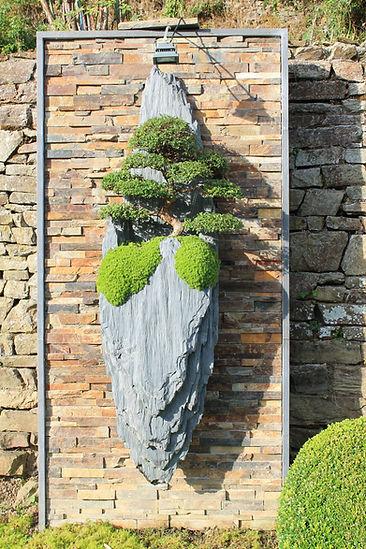gravity , sculpture unique de 300 kilos sculptéee par arnaud Desbois ,sculpteur de paysages et suspendues à un mur moderne, elle est sculptée en schiste et ornée d un orme de chine agé de 30 ans