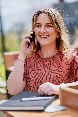 Roxanne Deurloo, Leading Light, talking on phone smiling with notebook