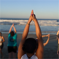 Image of a student practicing yoga on a beach.