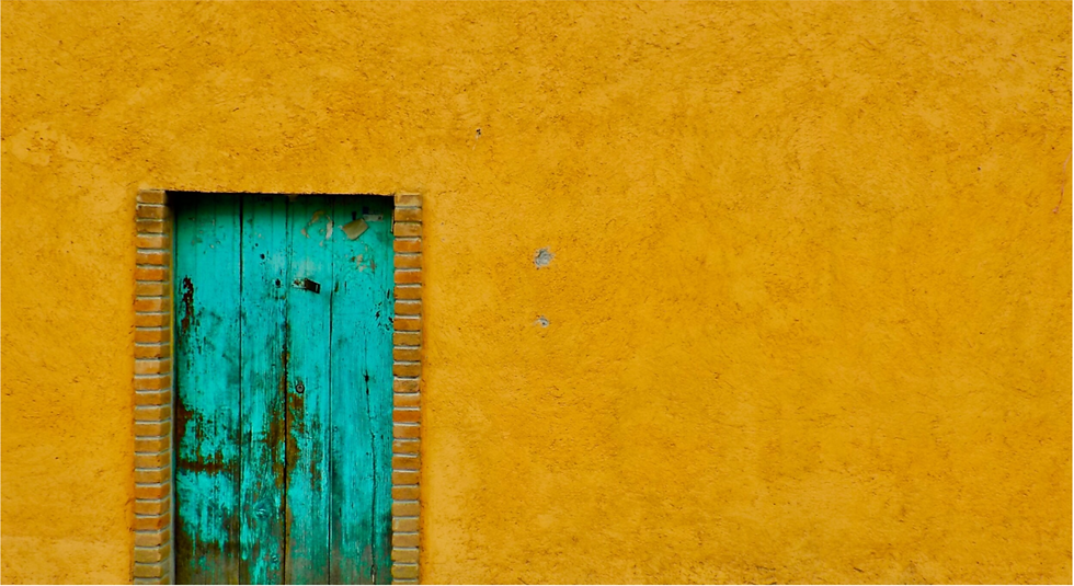 Yellow wall with a wooden teal door painted yellow in Mexico.