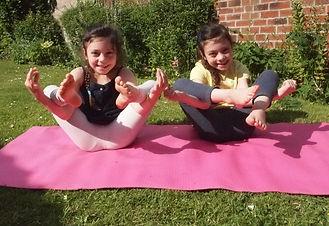 Two children doing flower pose yoga