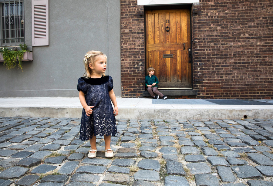 Young children on a cobblestone street.