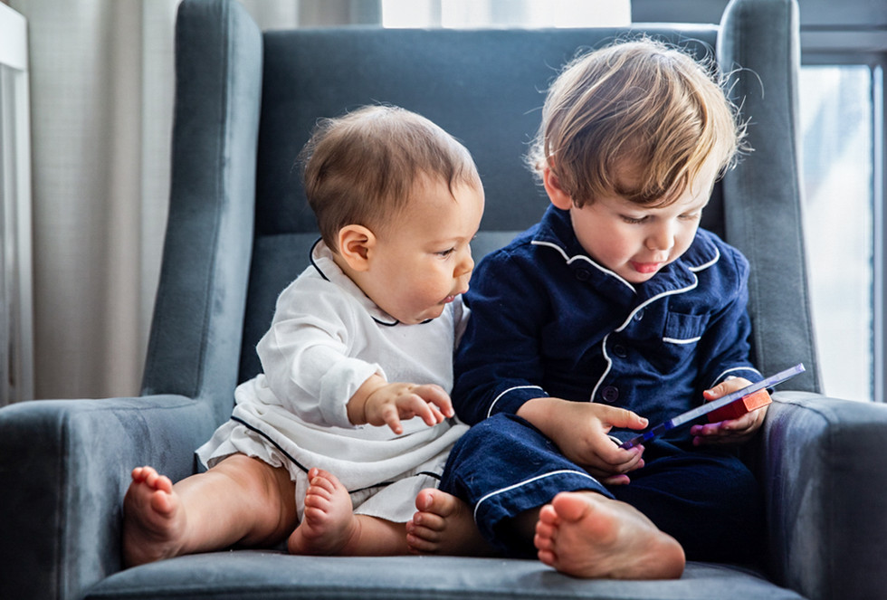 Baby and his brother looking at a small screen.