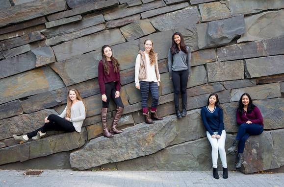 Teens standing on rocks.
