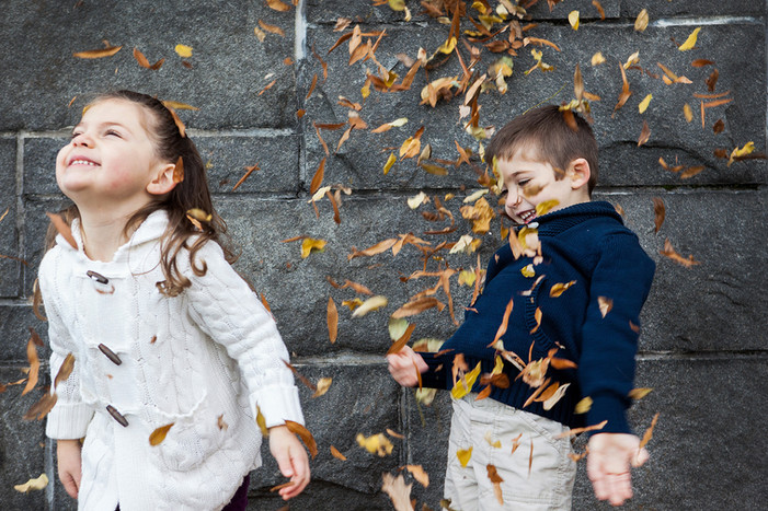 Kids playing in leaves.