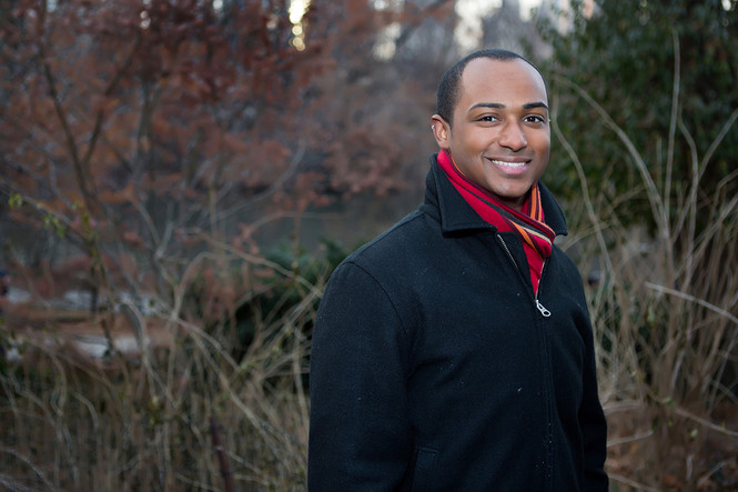 Black man in a coat in the park smiling.