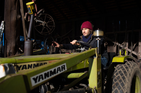 Man in a red hat driving a tractor.