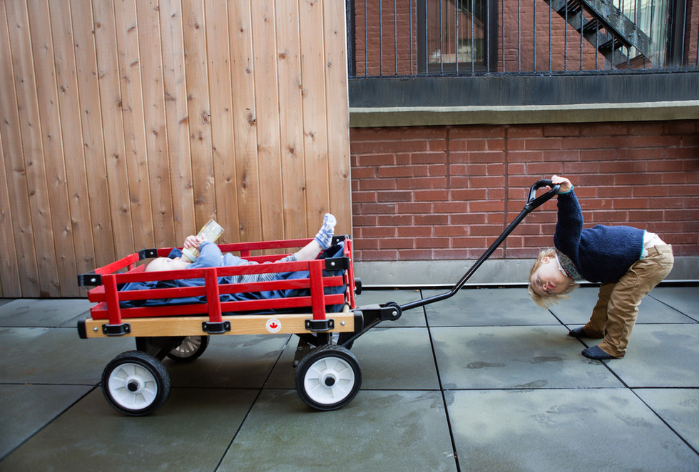 Older Brother pulls Baby in Red Wagon