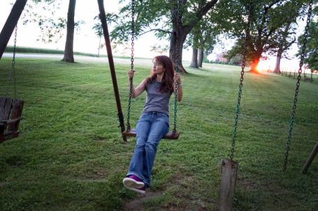 Woman on a swing at sunset.