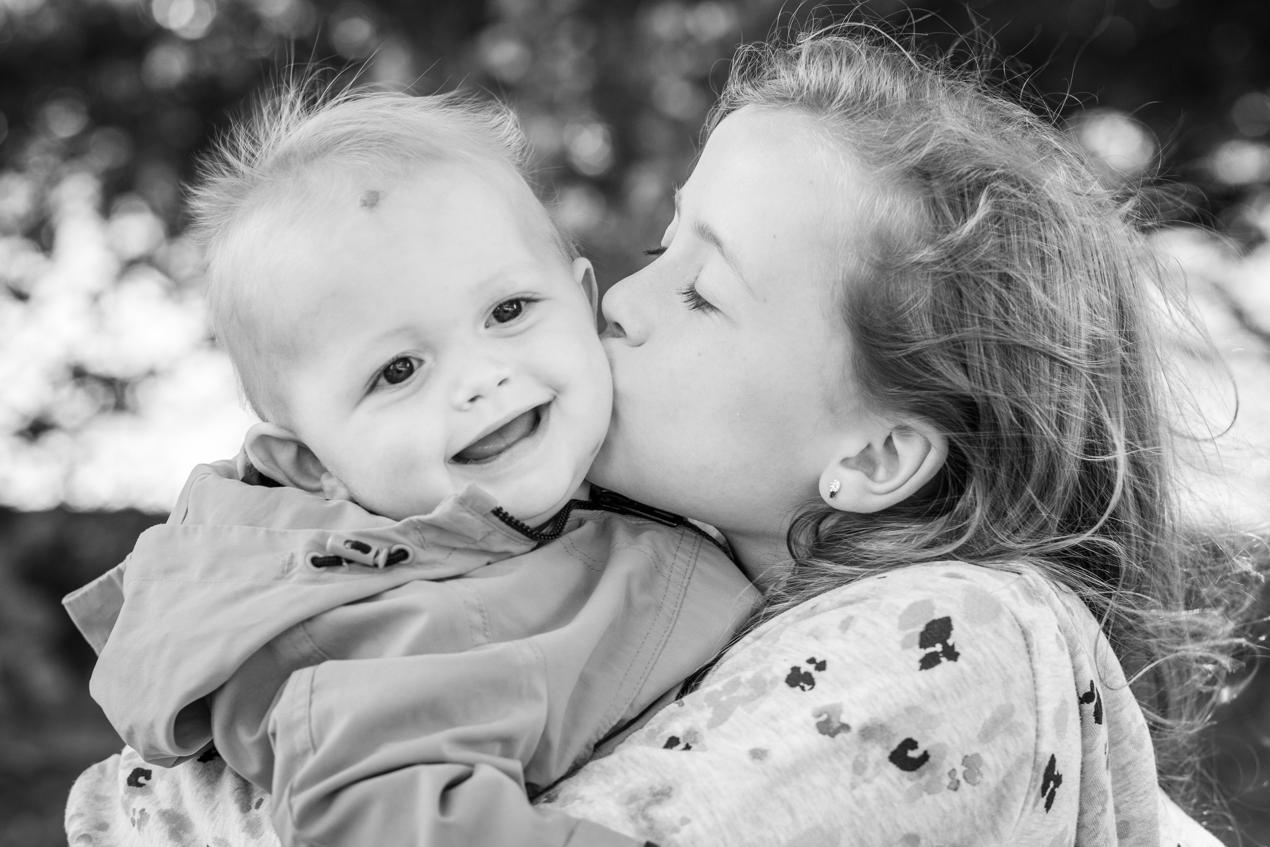 Swansea brother and sister kiss in a black and white photograph