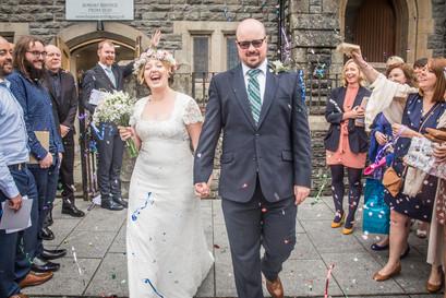 bride and groom walk through guests throwing confetti outside a swansea church wedding