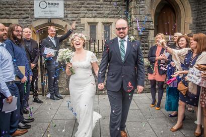bride and groom walk through confetti outside a swansea church wedding