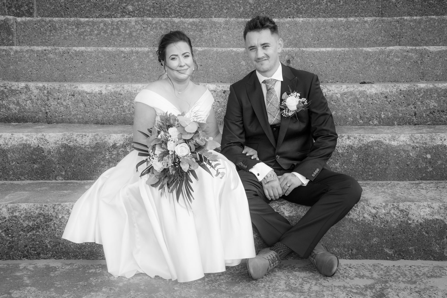 natural and elegant photo of a wedding couple sat on steps