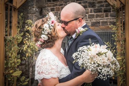 bride and groom kiss in a swansea wedding venue