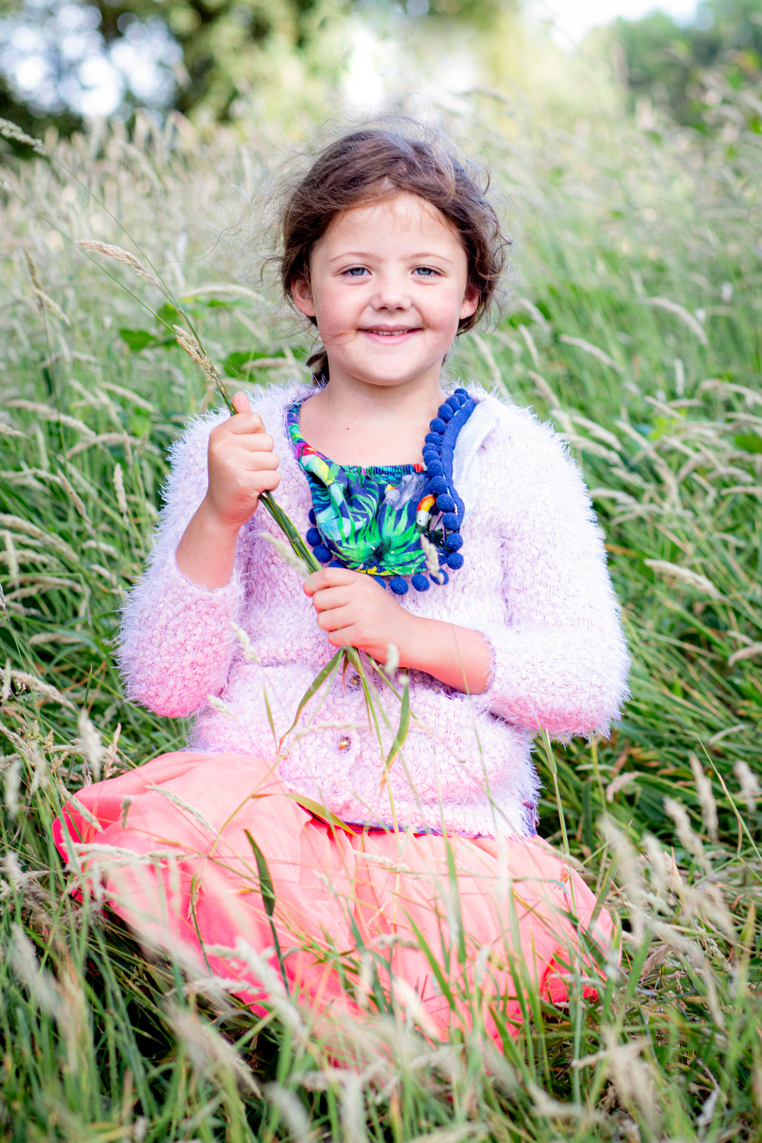 child excitedly holds grasses as she poses for a swansea photographer