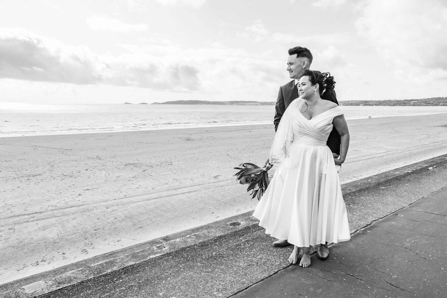 natural photograph of bride and groom standing in front of the mumbles looking out to sea
