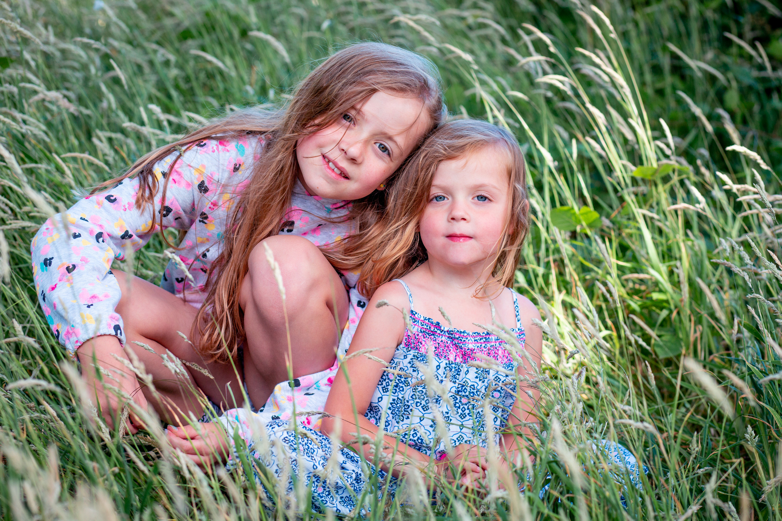 Two girls naturally pose in front of a swansea portrait photographer