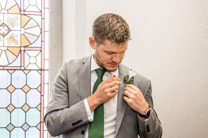 best man arranges his swansea button hole as photographer capture natural moments