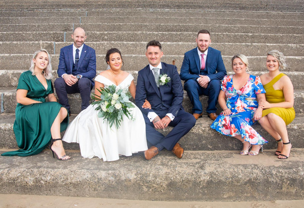small wedding party due to coronavirus sat on steps at swansea civic centre