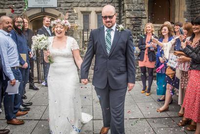 newly weds bride and groom walk through confetti shower outside a swansea church wedding